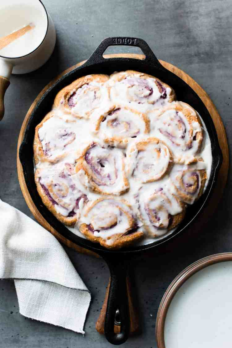 Vegan Coconut Ube Rolls in a cast iron skillet covered with coconut glaze.