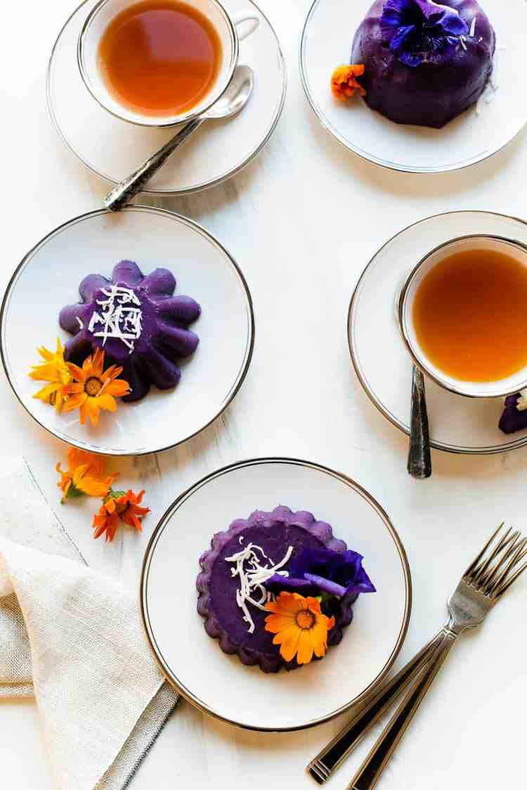 Ube Halaya molded into individual cakes, garnished with shredded coconut and edible flowers.