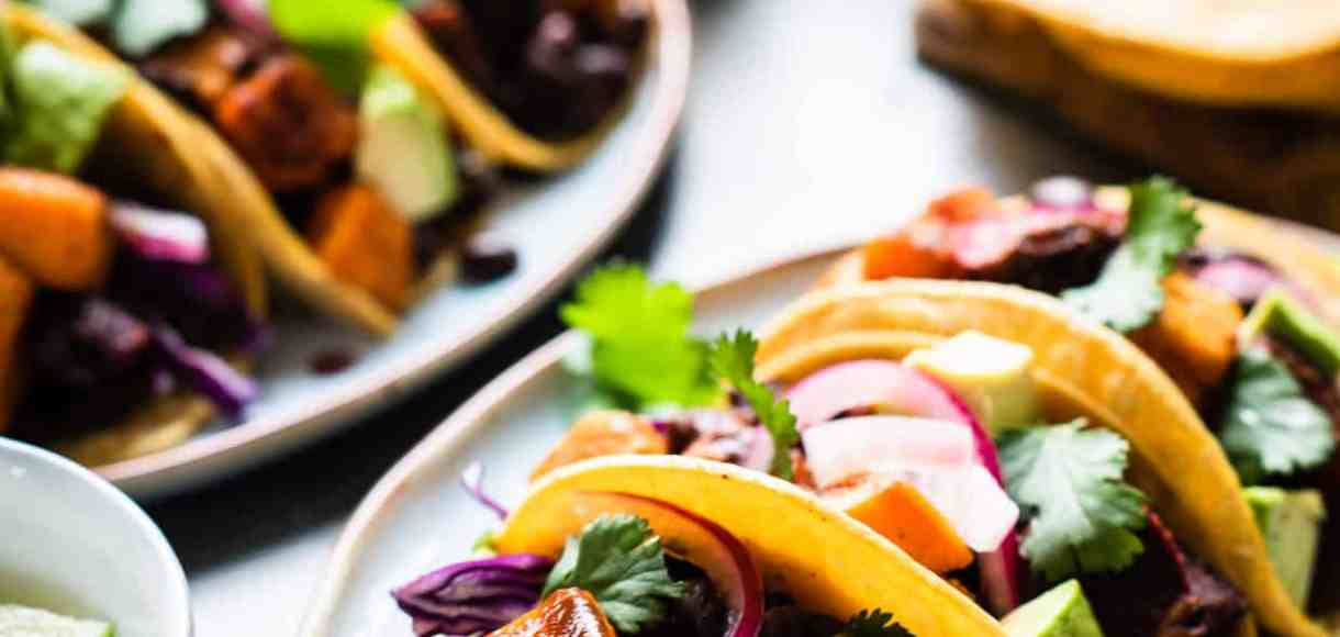 Chipotle-Spiced Sweet Potato Tacos garnished with red cabbage, cilantro and chipotle salsa on a platter.