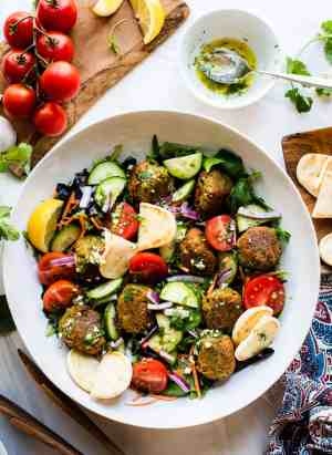 Falafel Salad with Lemon Garlic Dressing in a large bowl with pita bread.
