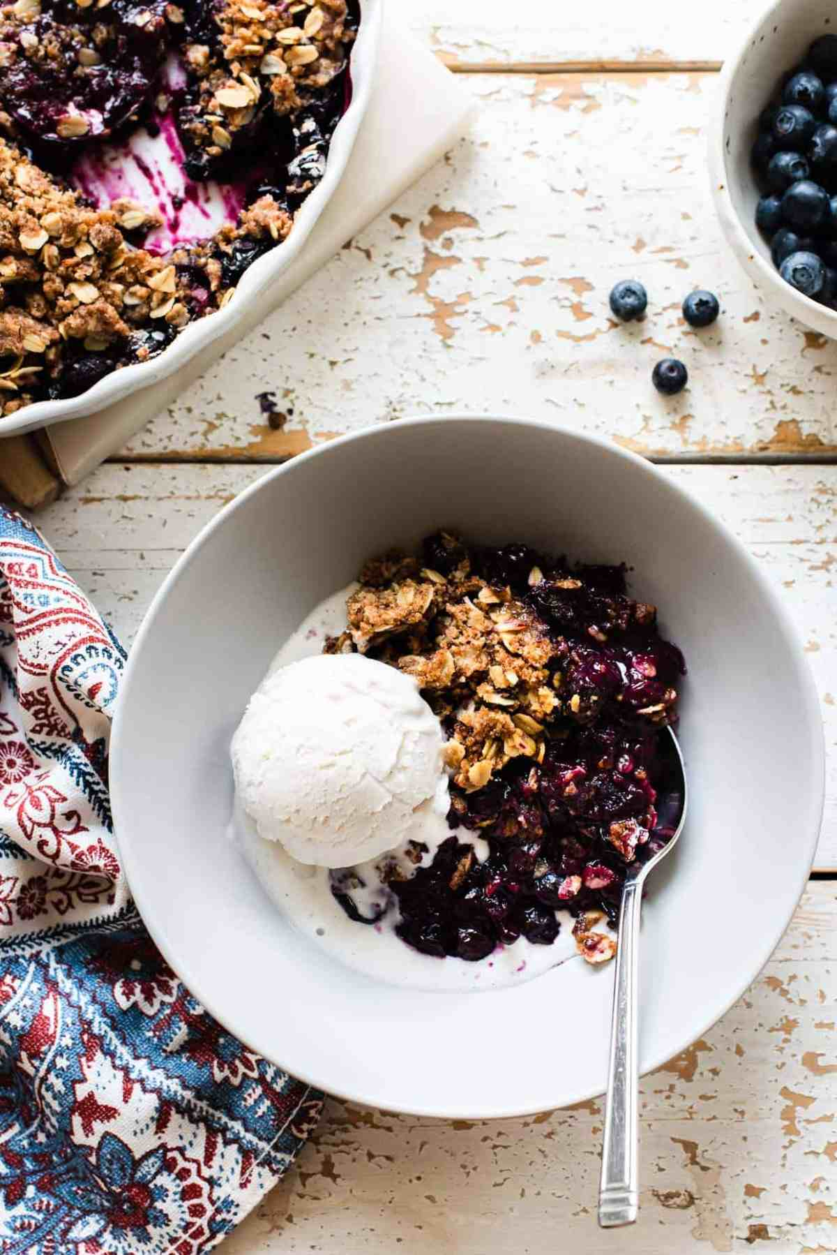 A white bowl filled with blueberry crisp and a scoop of vanilla ice cream on a rustic surface.