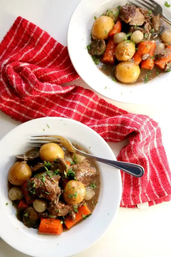 Two bowls of beef burgundy on a white table with a red towel.