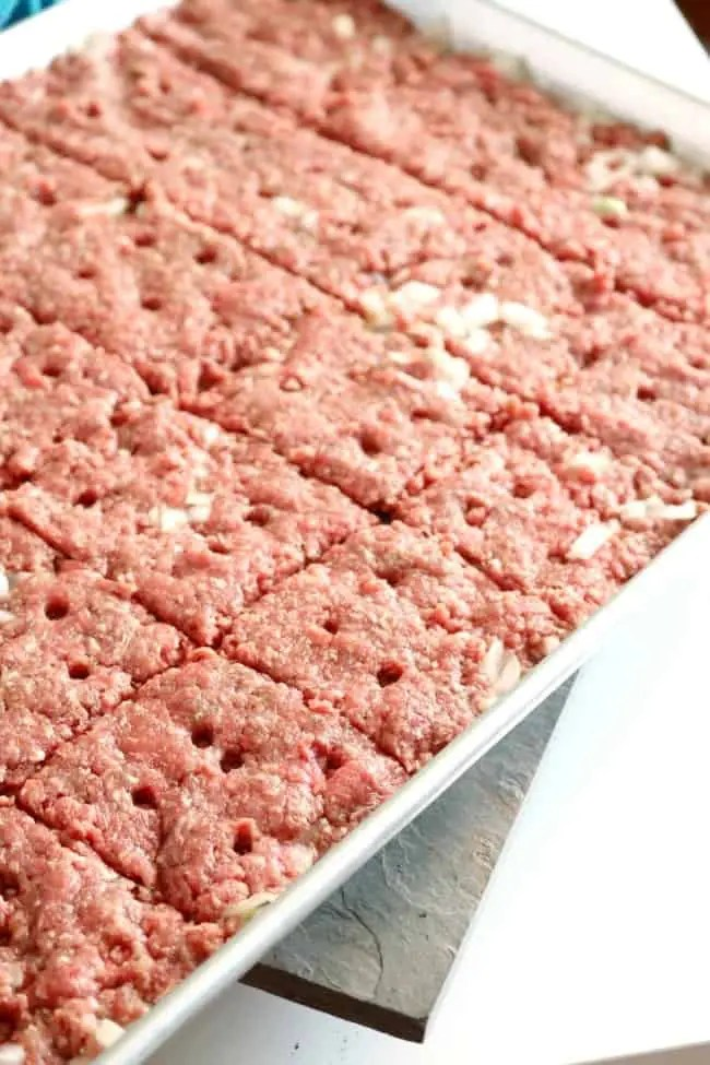 A tray of ground beef and onions formed into 24 patties and vented for steam.