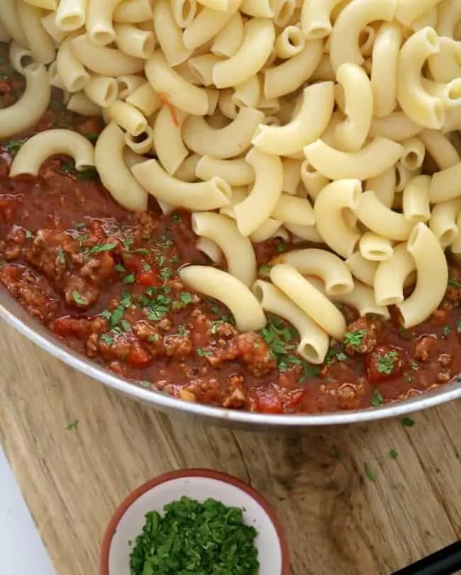 A pan of American goulash ready to be mixed with tomato-beef sauce and drained macaroni noodles.