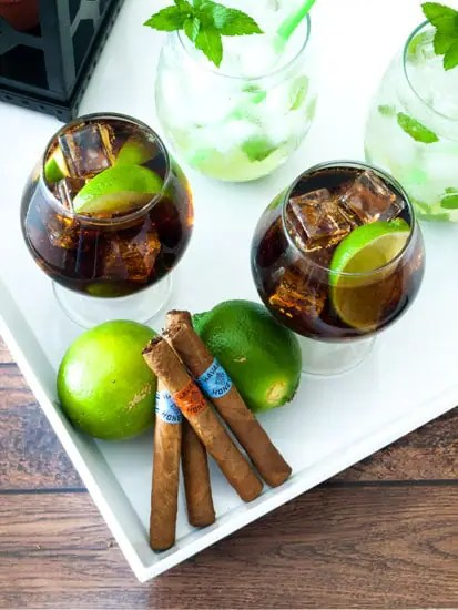 Cuba Libre cocktails on a white tray with lines and havana cigars