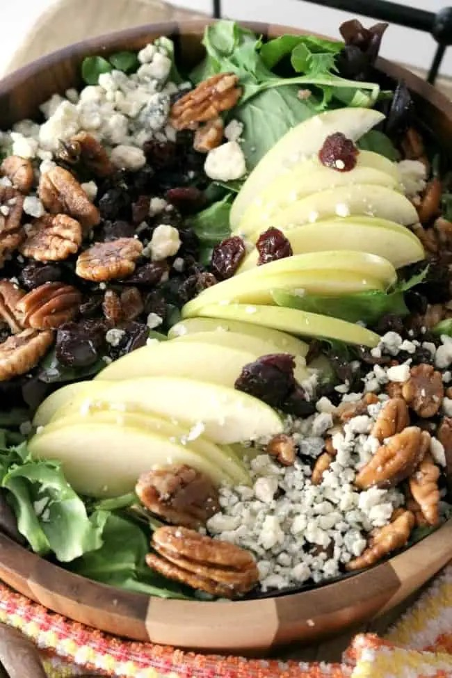 A 3/4 angle shot of Apple Pecan Blue Cheese Salad with Apple Vinaigrette in a wooden bowl.