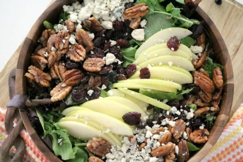 An overhead shot of Apple Pecan Blue Cheese Salad with Apple Vinaigrette in a wooden bowl.