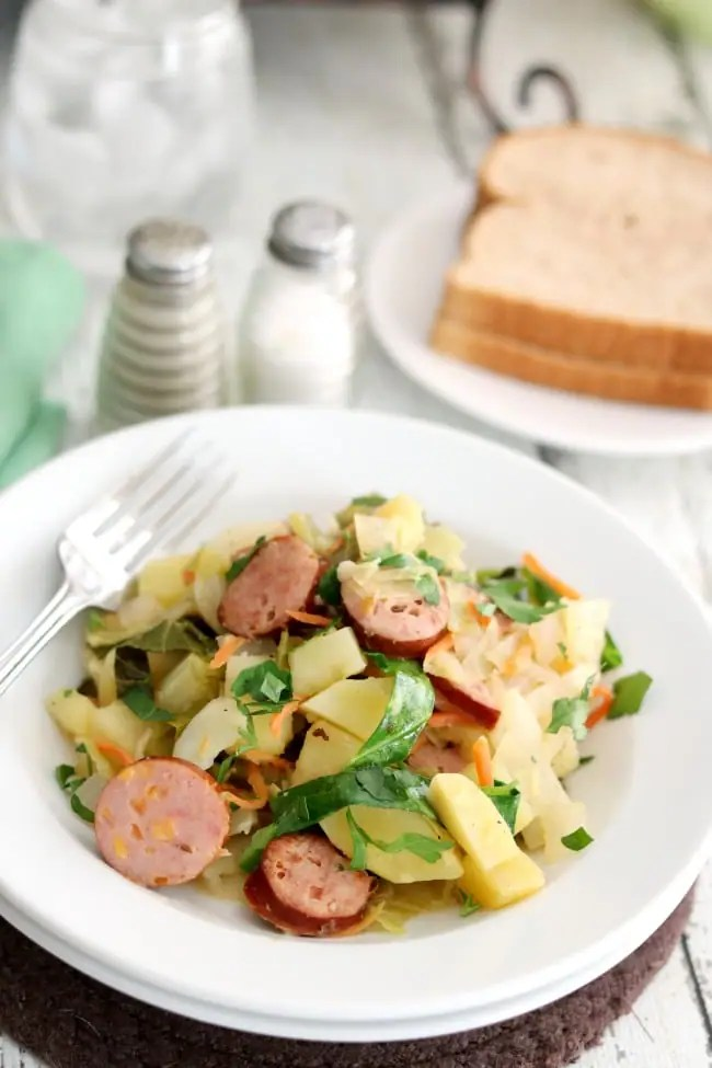 This German-inspired Smoked Sausage Recipe pairs sausage rounds with braised cabbage and potatoes and is seasoned with fennel and caraway. #Kroger #Hillshire Farm #Smoked Sausage