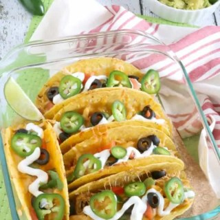 Tender and juicy Shredded Mexican Style Chicken is layered into crispy Taco shells, topped with shredded cheese and baked to golden perfection in the oven to create these Baked Chicken Tacos. What my family loves about it is that we can each add just whatever toppings we like in any quantity we chose. YUMM!