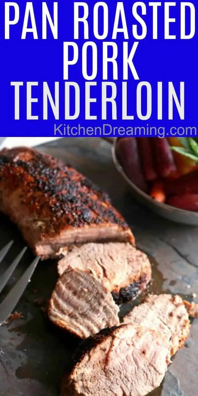 Roasted pork tenderloin on a dark slate tile with a bowl of rainbow carrots.
