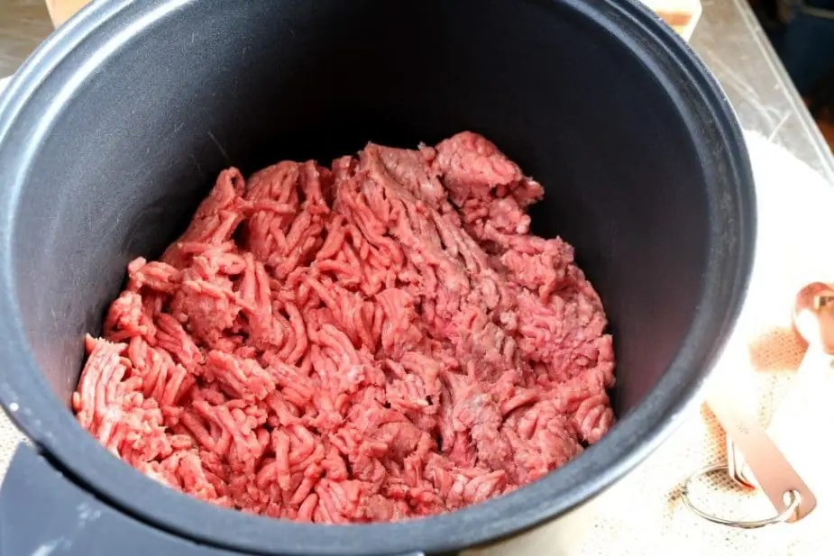 Lean ground beef in the slow cooker insert ready to be prepared for tacos.