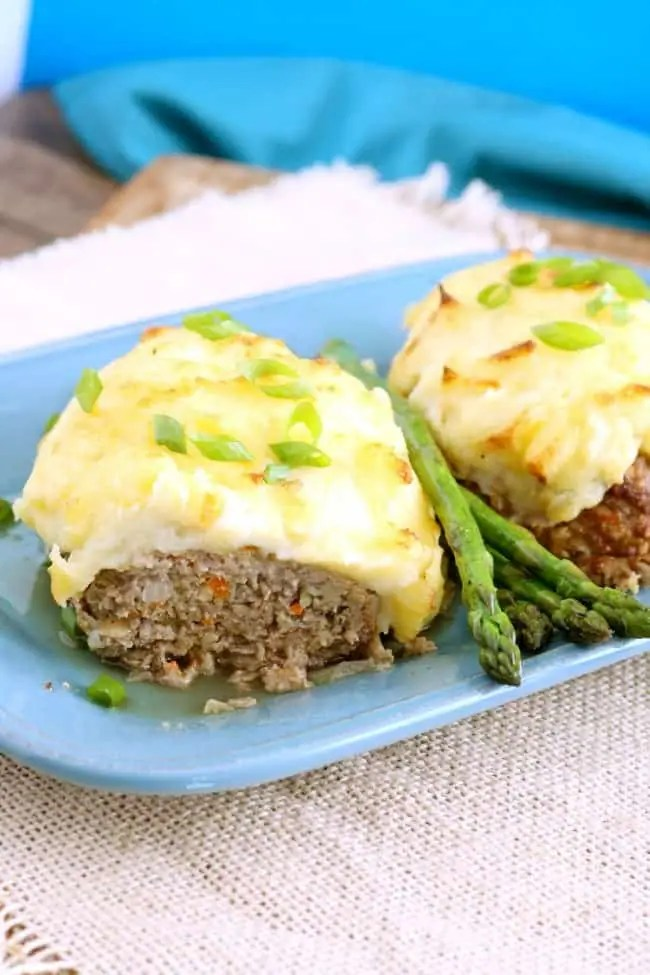 Mashed potato topped meatloaf on a blue serving plate with asparagus