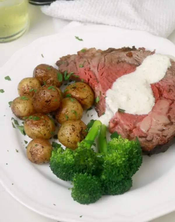 A piece of medium rare prime rib on a white plate with roasted baby potatoes and steamed broccoli.