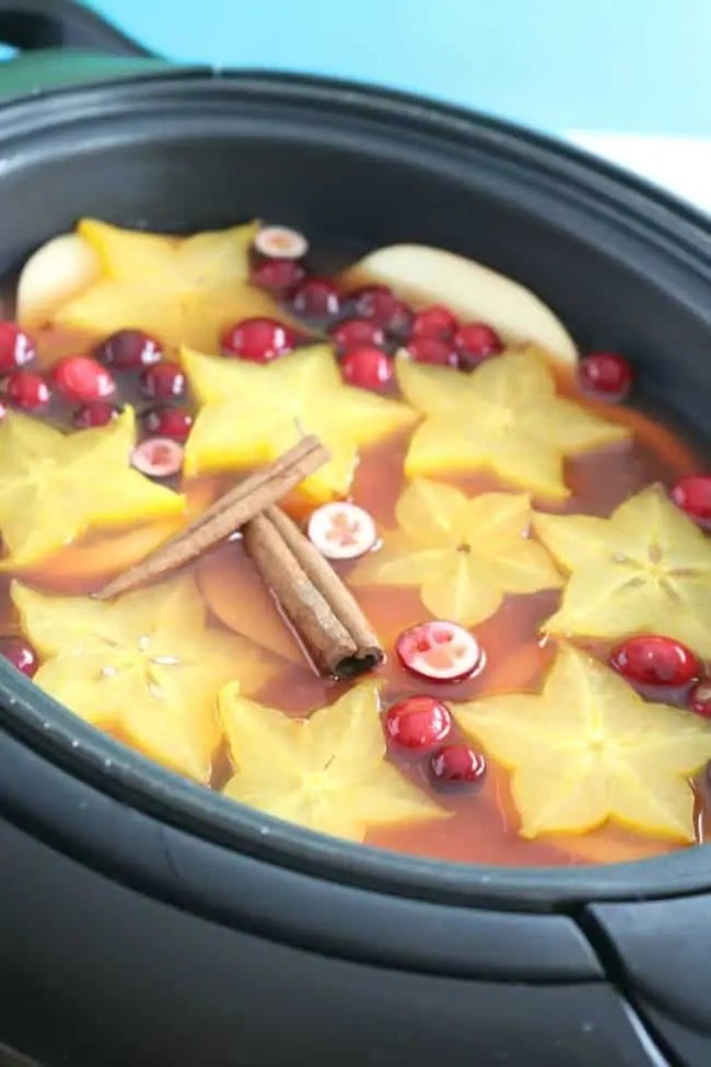 a slow cooker filled with warm holiday punch. slices of apples, oranges, star fruit, cranberries and cinnamon sticks float on top in a spectacular holiday display.