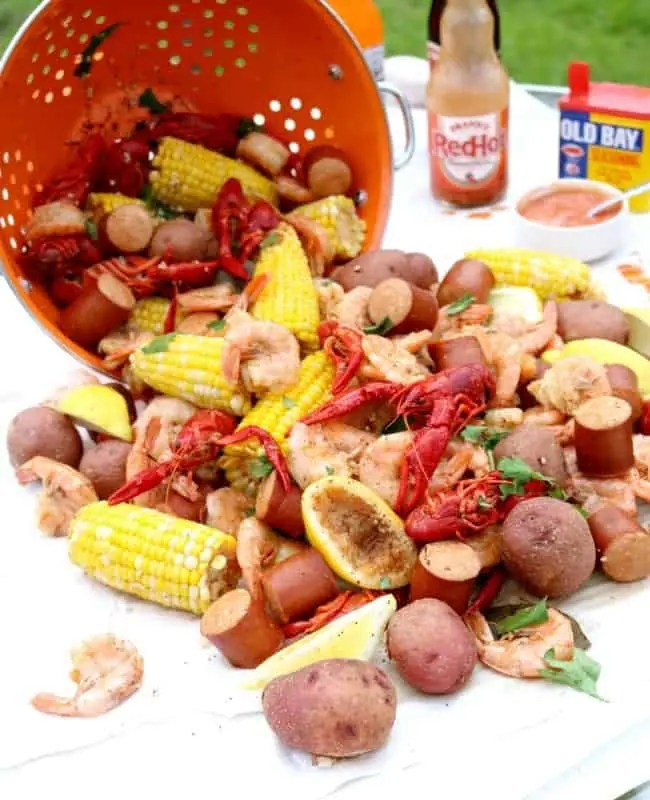 A lowcountry shrimp boil laid out on newspaper on a picnic table.