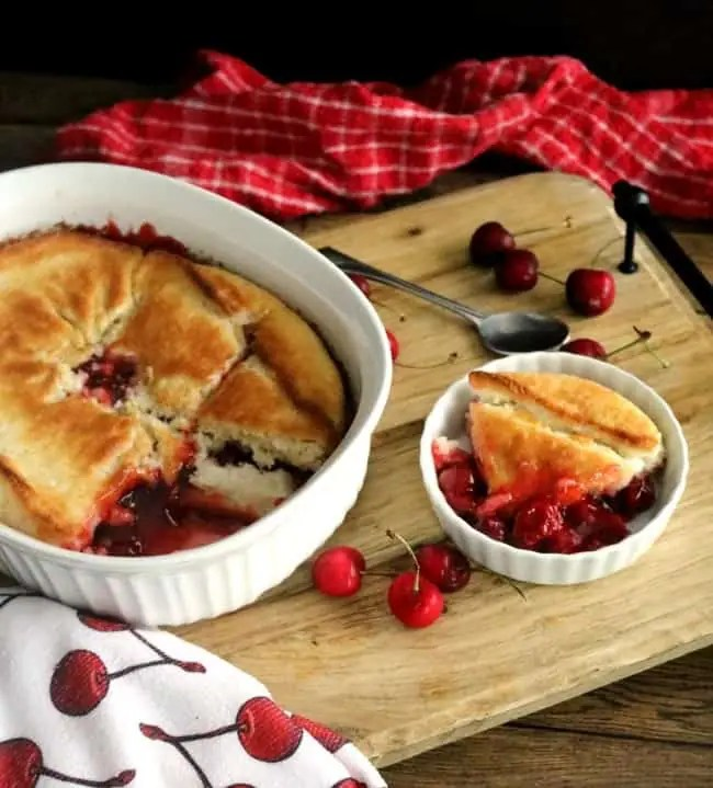 A casserole of cherry cobbler on a wooden cutting board next to a bowl of cherry cobbler