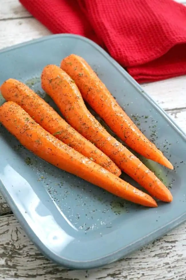 a plate of carrots ready to be roasted. Easy Oven Roasted Carrots are the perfect side for weeknight meals and holiday dinners.