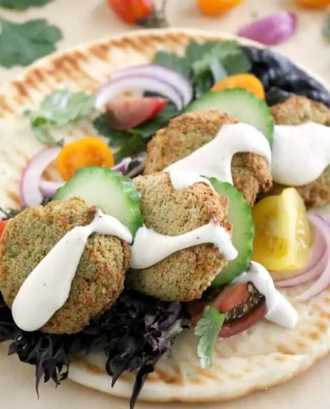 air fryer falafel in a pita with sliced cucumbers, red onions slices, diced tomatoes and lettuce and drizzled with tzatziki sauce.