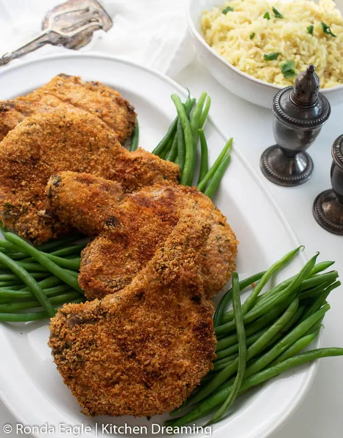 A serving plate filled with crispy air fryer pork chops which have been breaded and cooked to a perfect golden brown.