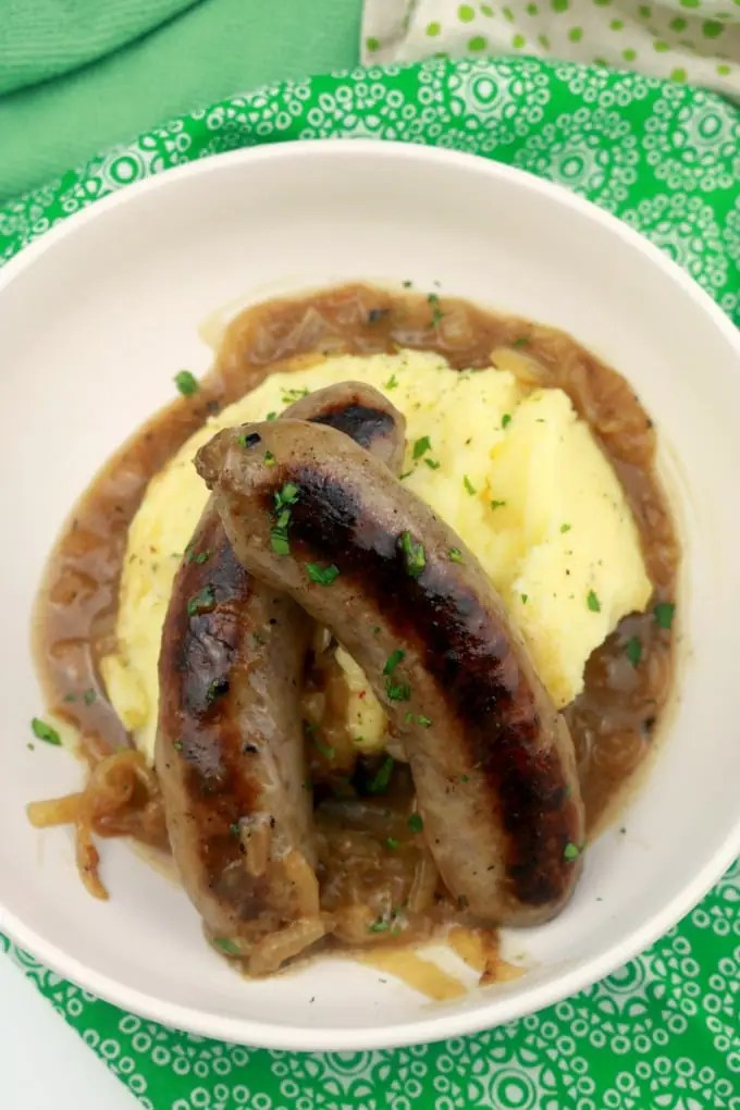 A bowl of bangers and mash in onon ale gravy