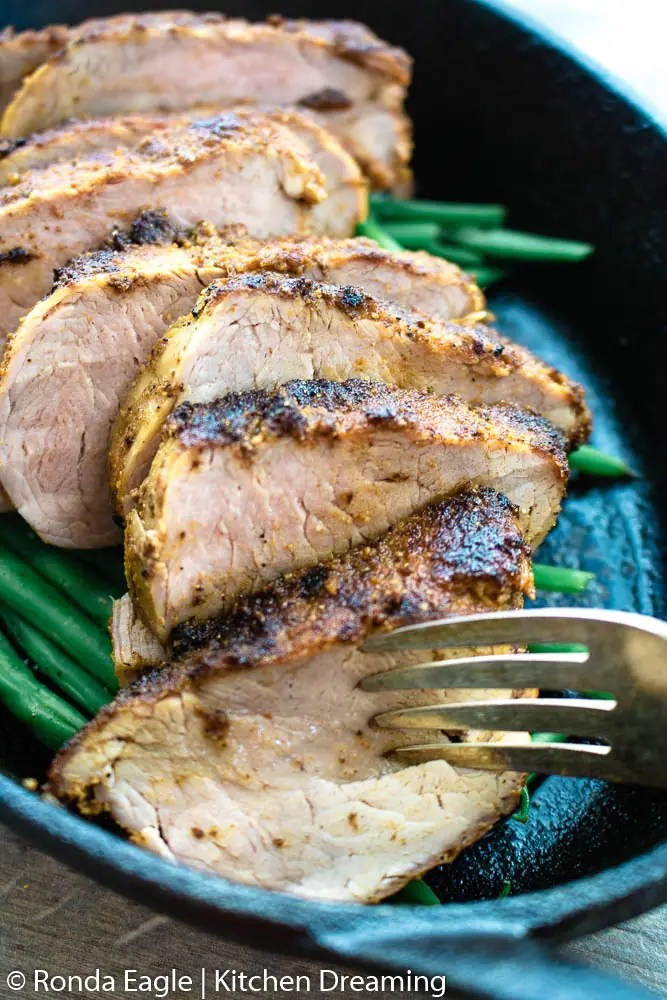 A close up image of an oblong cast iron skillet filled with roasted green beans and sliced pork tenderloin. A serving fork pierces the foremost piece of meat and juices are running out of the meat.