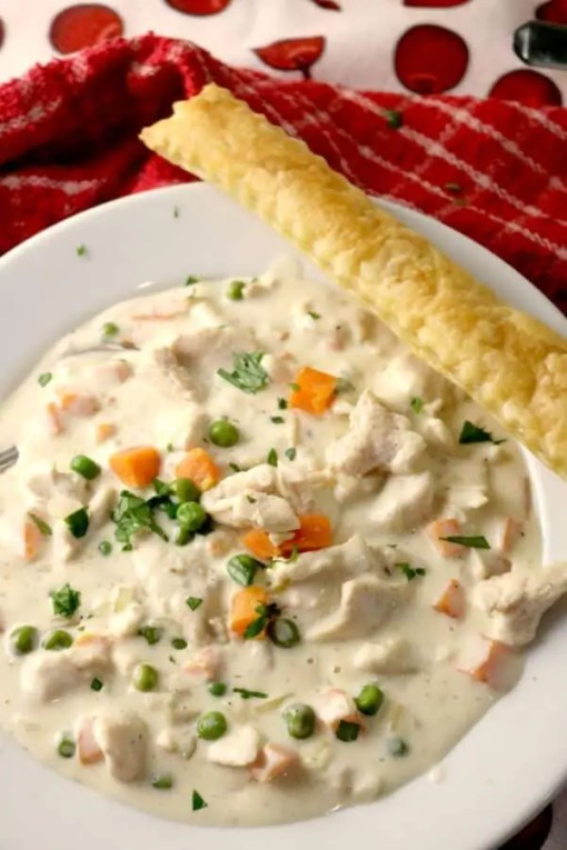 Chicken Pot Pie Soup in a white bowl with a Puff Pastry Stick laying across the top of the bowl. It is set on a red pinstripe towel.