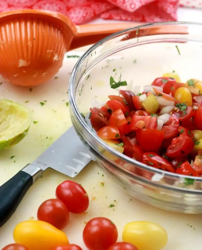 A bowl of fresh pico de gallo on a cutting board with a lime, a citrus juicer, and some fresh grape tomatoes.