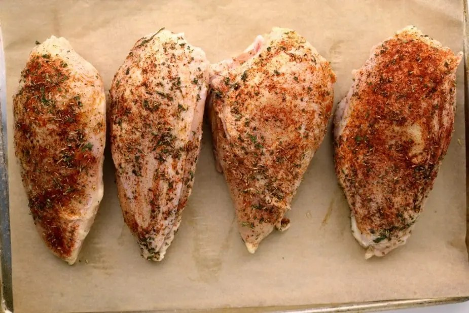 a rimmed backing sheet lined with parchment paper containing four seasoned bone-in chicken breasts ready to go into the oven.