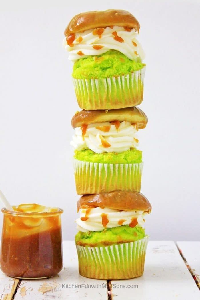A stack of three caramel apple cupcakes on a white wooden surface with jar of caramel on side