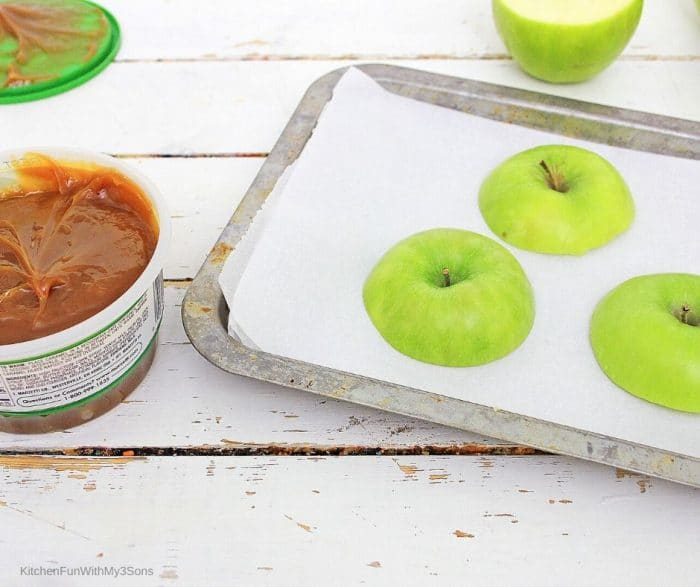 Apple slices for caramel apple cupcakes on a baking sheet ready to be dipped