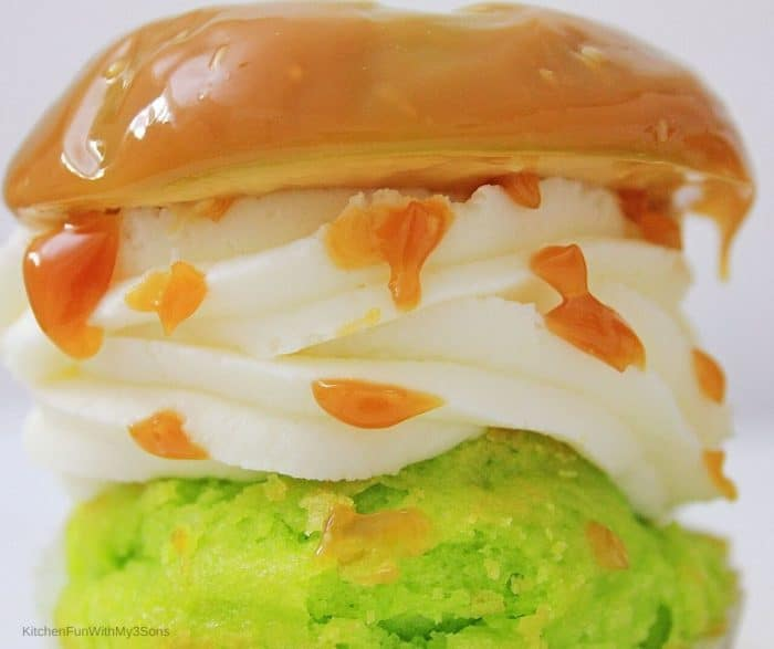 Up close picture of cupcake with icing and caramel apple on top