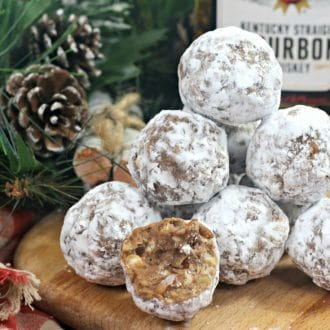 Stacked bourbon balls on a wood cutting board in front of Jim Beam bourbon