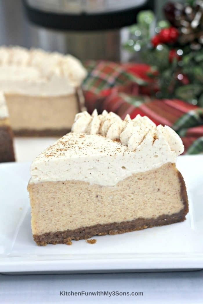 Up close picture of a slice of eggnog cheesecake on a plate in front of holiday decor