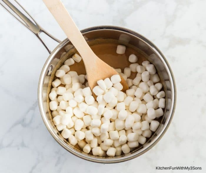 Mixing marshmallows into the butterscotch chip mixture for cereal bars