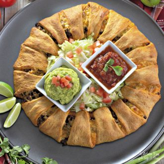 Super easy three ingredient crescent roll Taco Ring with ground beef. Add your toppings to customize your own. Perfect for Mexican night.