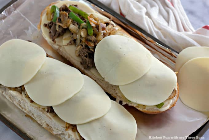 Covering Philly Cheesesteak Cheese Bread with deli-style provolone cheese slices
