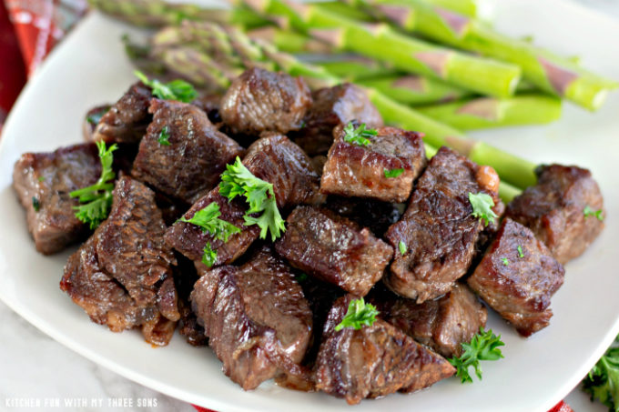 Garlic Butter Steak Bites on a white plate with steamed asparagus