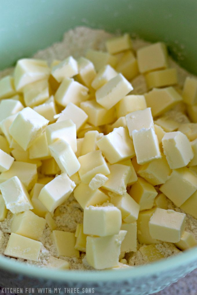 cubed butter in flour in a mint green bowl