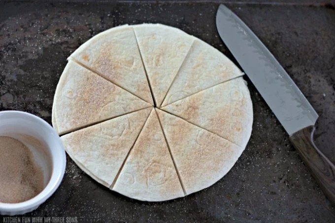 cutting flour tortillas into wedges to make cinnamon chips