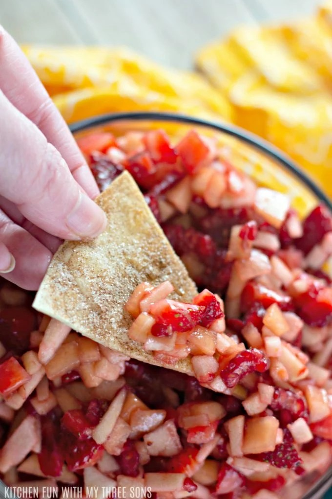 dipping a cinnamon sugar chip into a bowl of fruit salsa