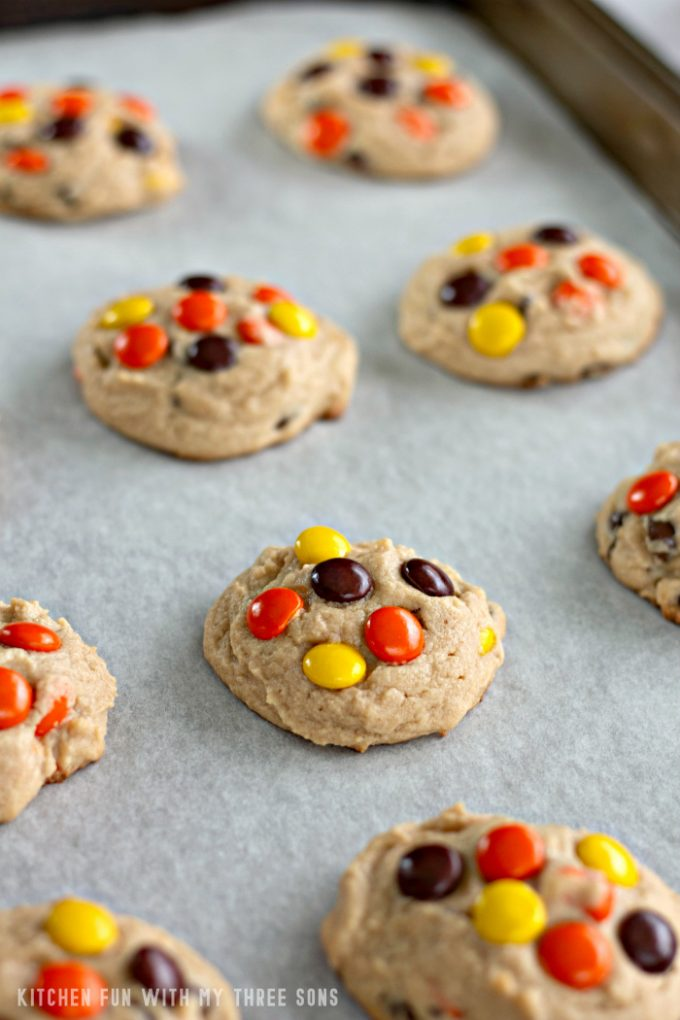 Reese's Pieces Peanut Butter Cookies on a parchment paper lined cookie sheet