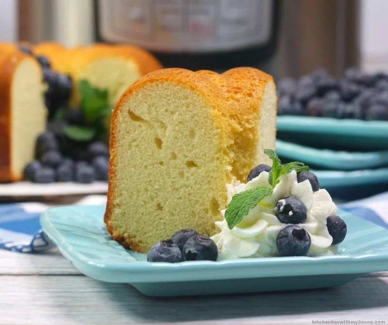 slice of instant pot pound cake on a blue plate with blueberries