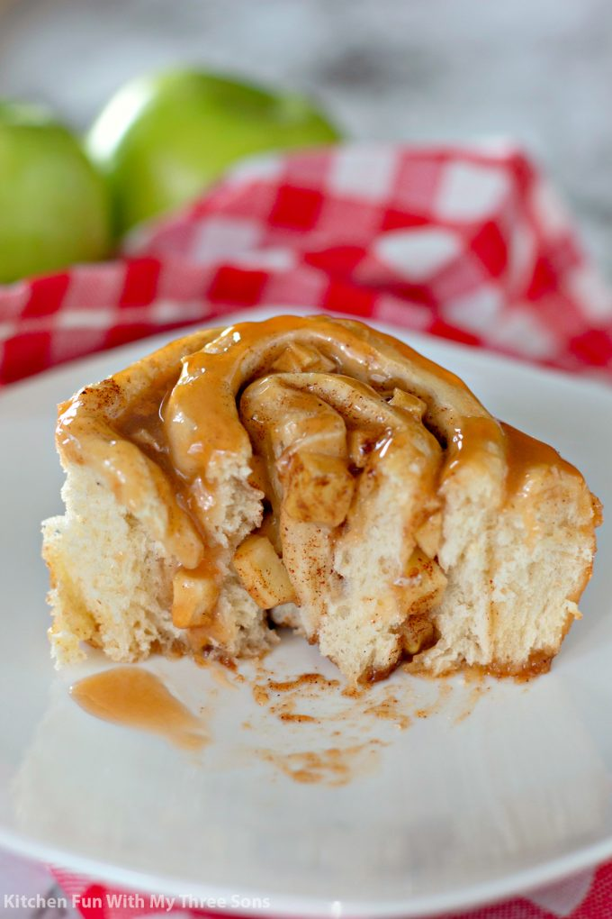 a Caramel Apple Cinnamon Roll cut in half and sitting on a white plate