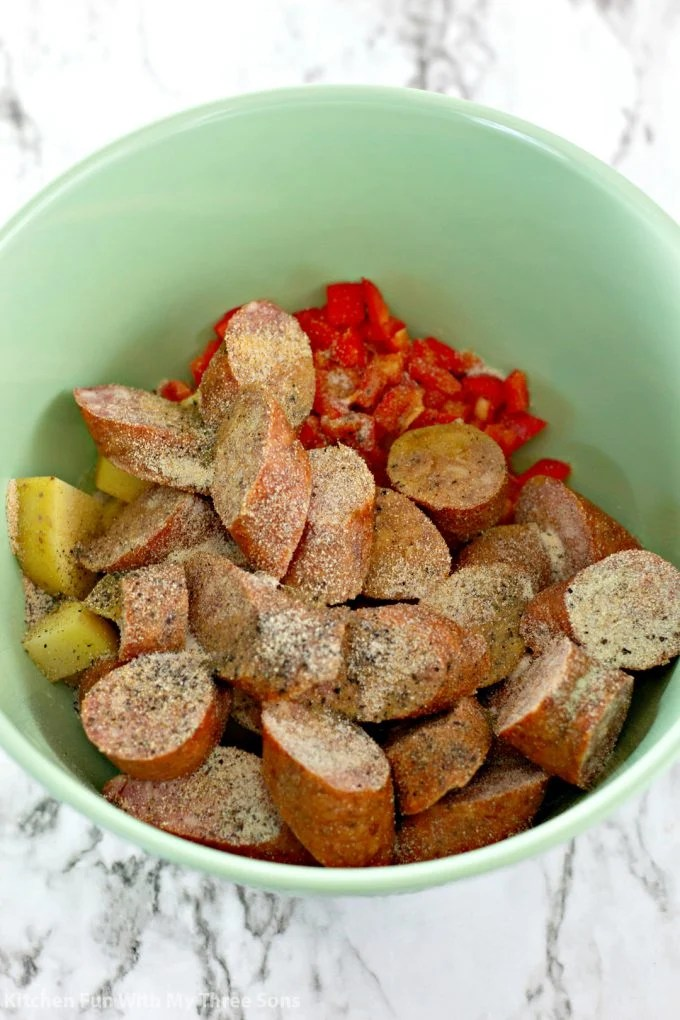 mixing kielbasa and potatoes and peppers with seasoning and olive oil in a mint green bowl