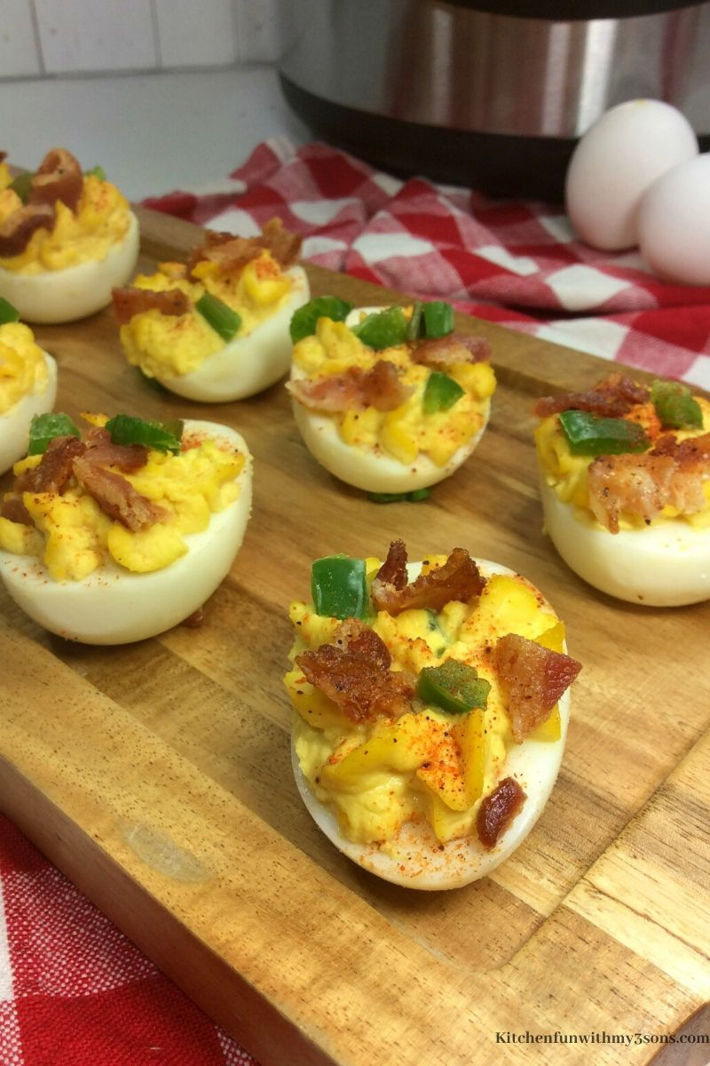 jalapeno bacon deviled eggs in a cutting board