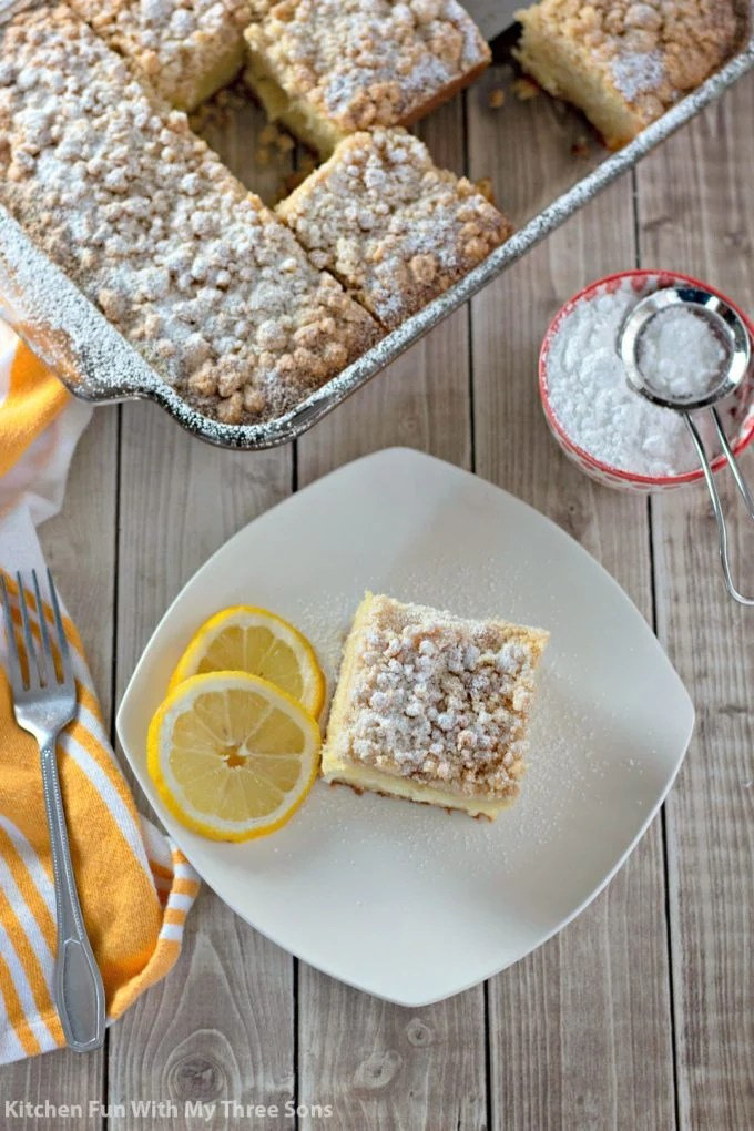 Lemon Cream Cheese Coffee Cake on a white plate with a yellow napkin on a light wood table