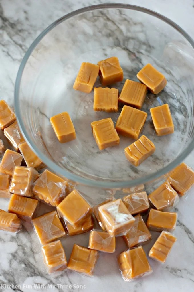 unwrapping caramels and pouring into a clear bowl
