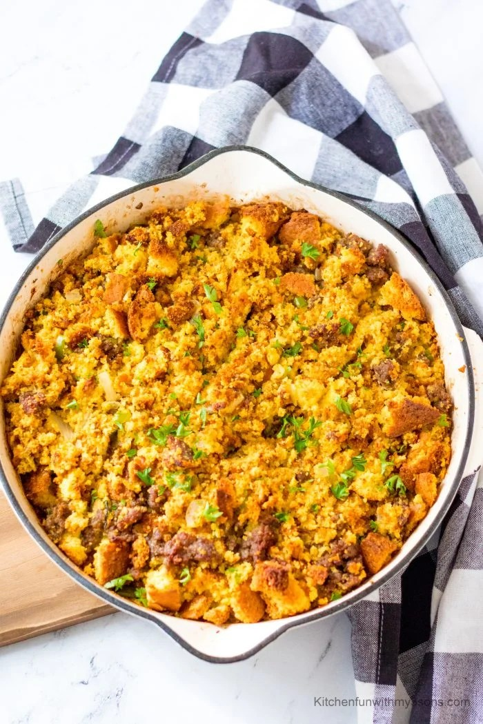Best Ever Sausage Cornbread Stuffing on a wooden tray next to a patterned cloth.