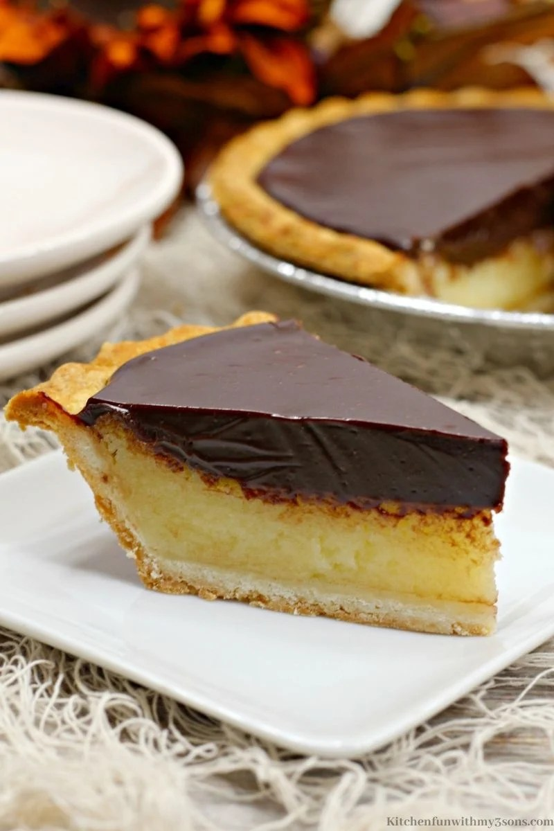 Close up of your Chocolate Buttermilk Pie with the whole pie behind it with extra serving plates.