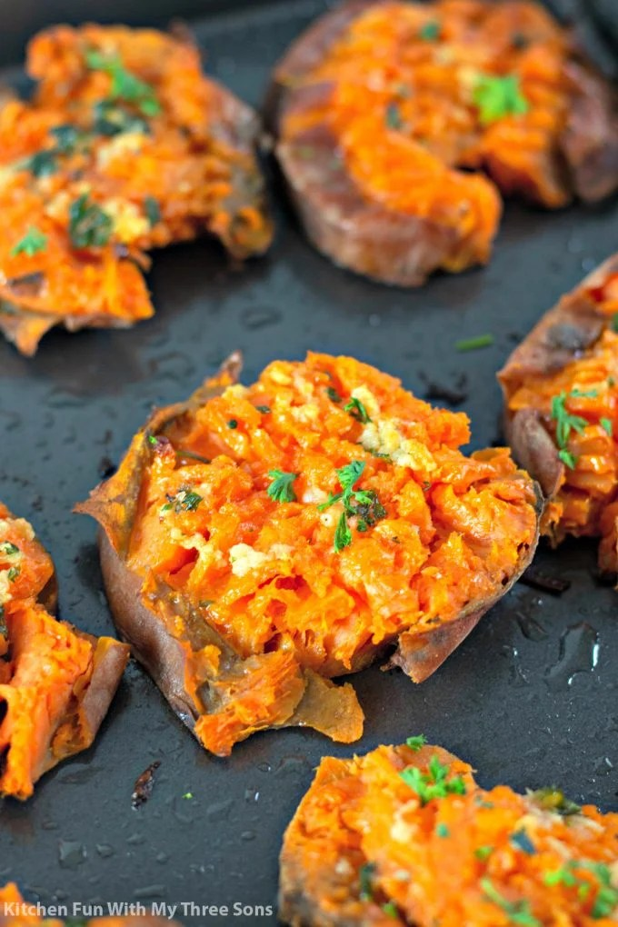 freshly baked Garlic Butter Smashed Sweet Potatoes on a cookie sheet